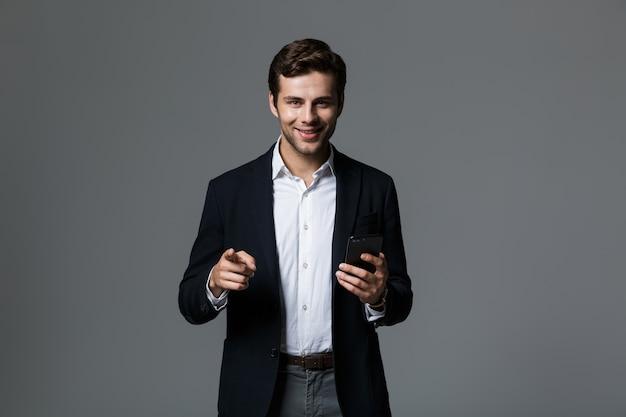 Portret szczęśliwy młody biznesmen ubrany w garnitur na białym tle nad szarą ścianą, trzymając telefon komórkowy, wskazując palcem
