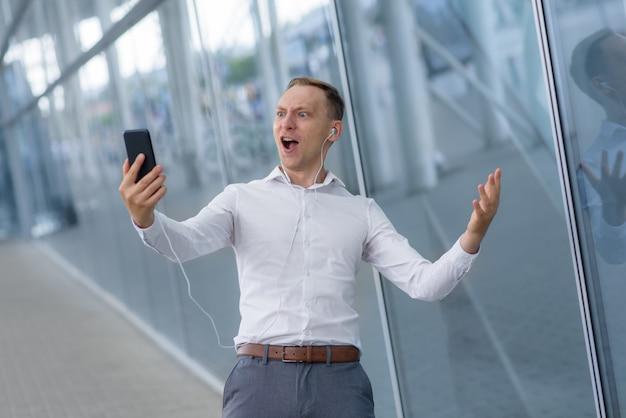 Portret szczęśliwy młody biznesmen w słuchawkach. mężczyzna otrzymał bardzo dobre wieści.