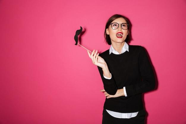 Portret szczęśliwy młody bizneswoman z papierowym wąsem