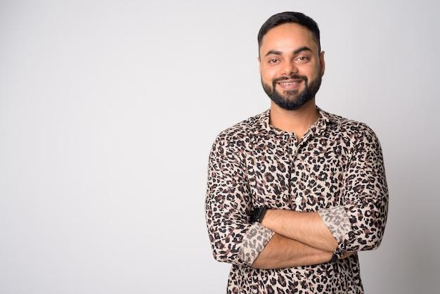 Portret szczęśliwy młody brodaty mężczyzna indyjski uśmiechając się z rękami skrzyżowanymi