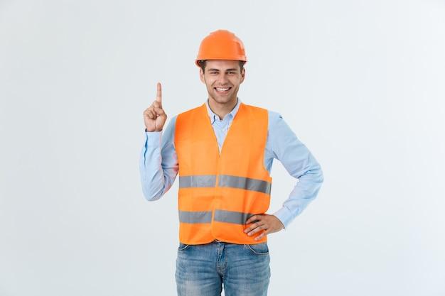 Portret szczęśliwy młody brygadzista z pomarańczową kamizelką na białym tle nad białym tłem.