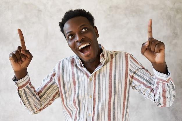 Portret szczęśliwy młody ciemnoskóry facet ubrany w pasiastą koszulę patrząc w górę z szeroko otwartymi ustami