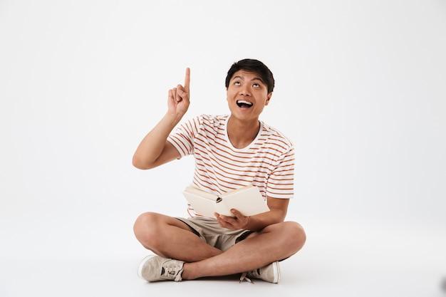 Portret szczęśliwy młody człowiek azjatyckich siedzi ze skrzyżowanymi nogami