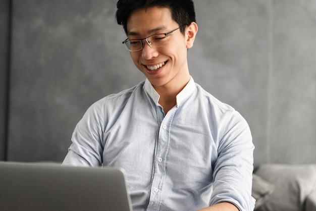 Portret szczęśliwy młody człowiek azji za pomocą laptopa