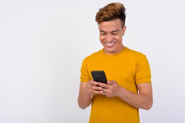 Portret szczęśliwy młody człowiek azji za pomocą telefonu na białej ścianie