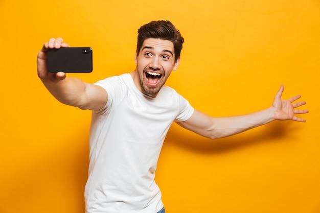 Portret szczęśliwy młody człowiek bierze sefie