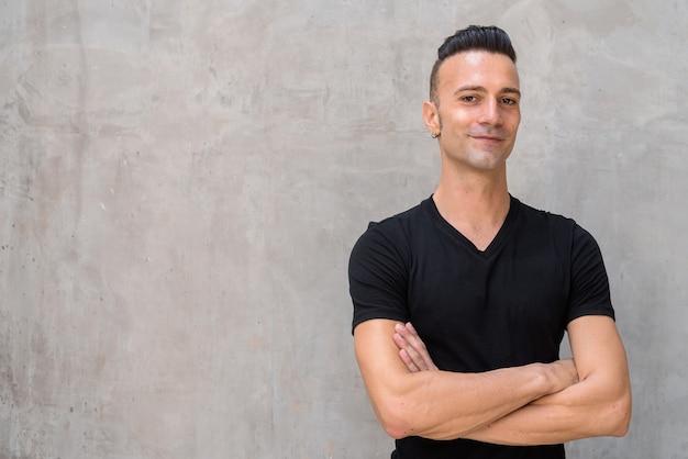 Portret szczęśliwy młody człowiek jest ubranym czarną koszulkę z podcięciem