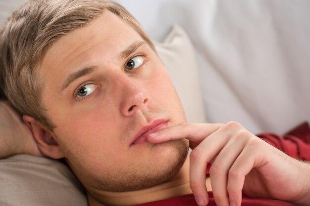 Portret szczęśliwy młody człowiek kłaść na kanapie w myśli