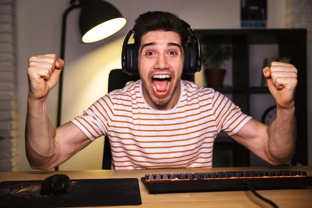 Portret szczęśliwy młody człowiek krzyczy podczas grania w gry wideo na komputerze, na sobie słuchawki i za pomocą podświetlanej kolorowej klawiatury