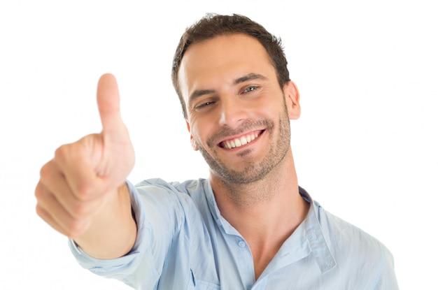 Portret szczęśliwy młody człowiek pokazuje kciuk w górę znak na białym tle