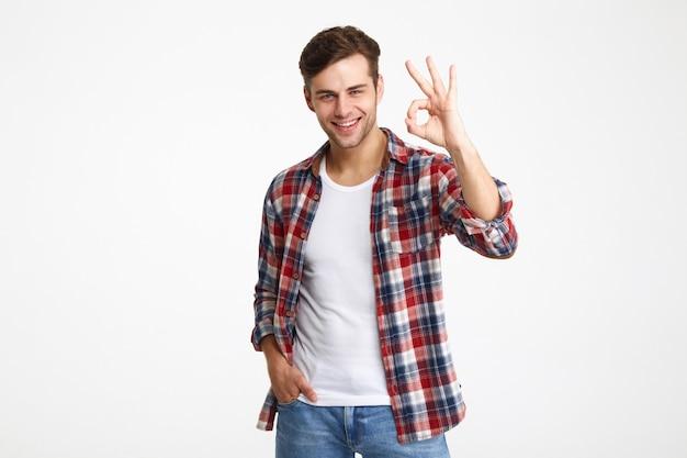 Portret szczęśliwy młody człowiek pokazuje ok gest