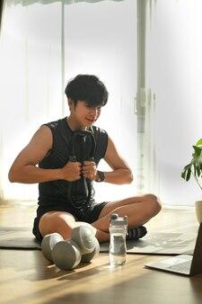 Portret szczęśliwy młody człowiek siedzi na jogi na matę do jogi i ćwiczenia w salonie.