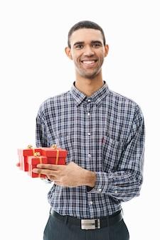 Portret szczęśliwy młody człowiek ubrany w kraciastą koszulę stojący nad białym, trzymając małe pudełka na prezent