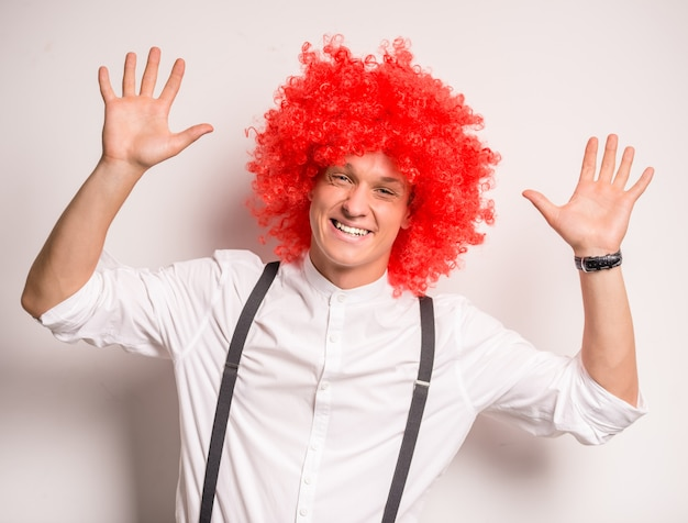 Portret szczęśliwy młody człowiek w czerwonej peruce.