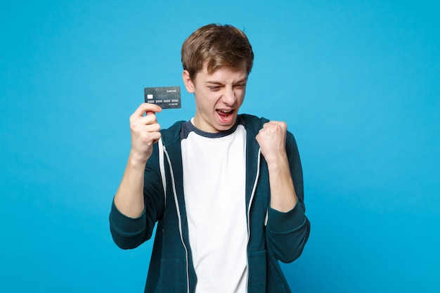 Portret szczęśliwy młody człowiek w zwykłych ubraniach, trzymając kartę kredytową, robi gest zwycięzcy na białym tle na niebieskiej ścianie. ludzie szczere emocje, koncepcja stylu życia.