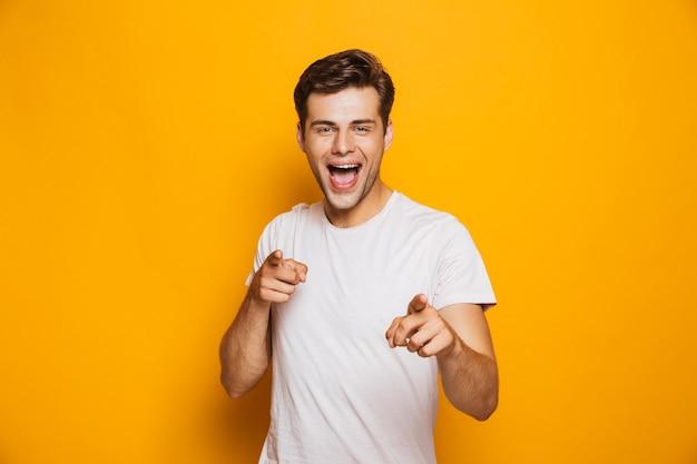 Portret szczęśliwy młody człowiek, wskazując palcami na aparat