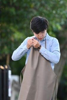 Portret szczęśliwy młody człowiek z azji ma na sobie brązowy fartuch w swoim ogrodzie.