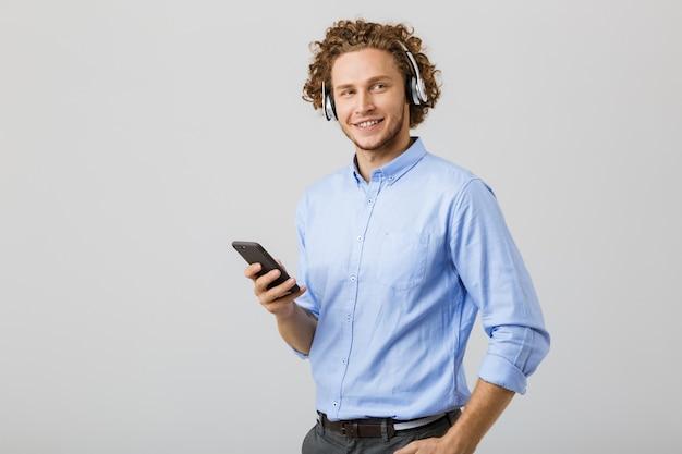 Portret szczęśliwy młody człowiek z kręconymi włosami na białym tle