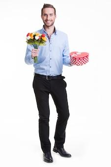 Portret szczęśliwy młody człowiek z kwiatami i prezentem - na białym tle.
