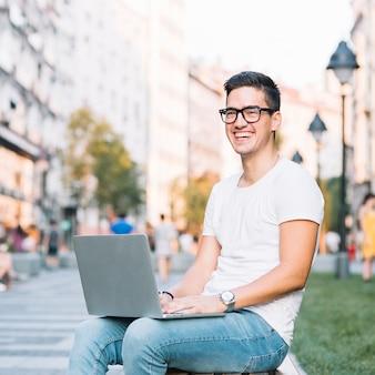 Portret szczęśliwy młody człowiek z laptopem