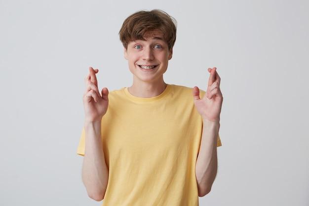 Portret szczęśliwy młody człowiek z palcem skrzyżowanym