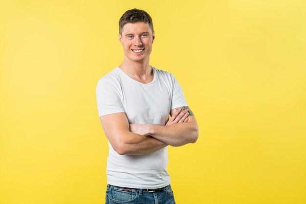 Portret szczęśliwy młody człowiek z ręką krzyżował patrzeć kamery pozycję przeciw żółtemu tłu