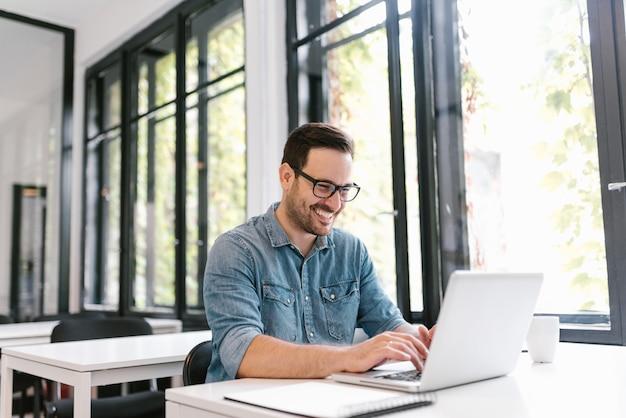 Portret szczęśliwy młody freelancer używa laptop.