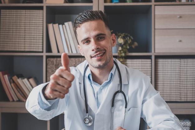 Portret szczęśliwy młody kaukaski lekarz mężczyzna pokazuje kciuk w górę daje zalecenie klinice. uśmiechnięty mężczyzna lekarz rodzinny lub terapeuta polecają dobrą jakość usług w prywatnym szpitalu. koncepcja medycyny.