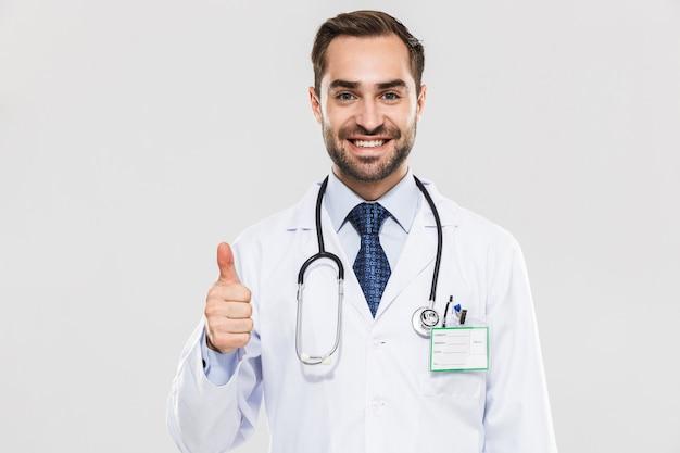 Portret szczęśliwy młody lekarz medycyny z stetoskopem uśmiechający się i pokazujący kciuk w górę na białym tle nad białą ścianą