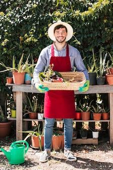 Portret szczęśliwy młody męski ogrodnik trzyma doniczkowe rośliny w koszu