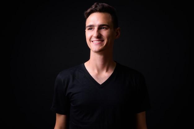 Portret szczęśliwy młody przystojny mężczyzna myśli i patrząc w górę