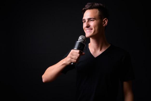 Portret szczęśliwy młody przystojny mężczyzna myśli podczas używania mikrofonu