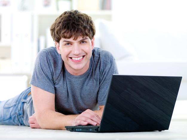 Portret szczęśliwy młody przystojny mężczyzna z laptopem - w pomieszczeniu