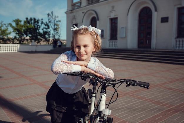 Portret szczęśliwy mody małe dzieci, zabawy z rowerem w mieście.