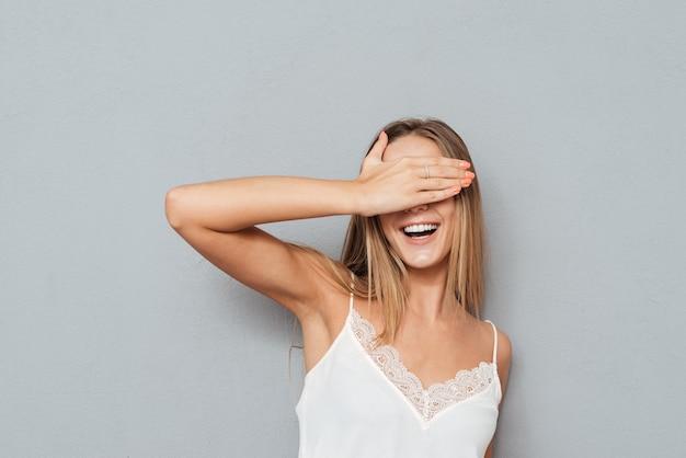 Portret szczęśliwy nastolatek żeński zakrywający oczy na białym tle na szarym tle