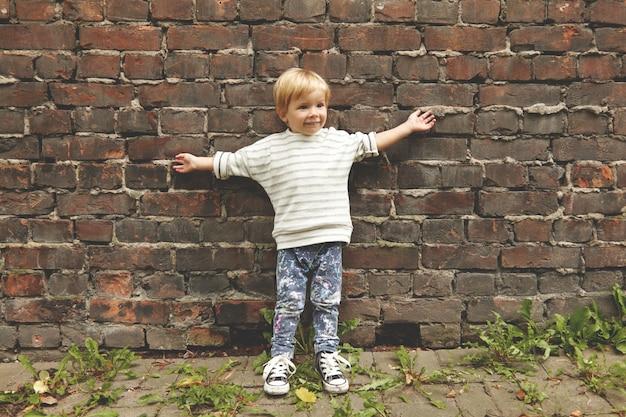 Portret szczęśliwy nieostrożny mały chłopiec. malutki dzieciak stojący przy ceglanej ścianie, wyciągający ręce na zewnątrz. nosi t-shirt w paski, codzienne dżinsy w kolorowe plamki, gumowe buty w stylu grunge. wokół rosną mlecze.