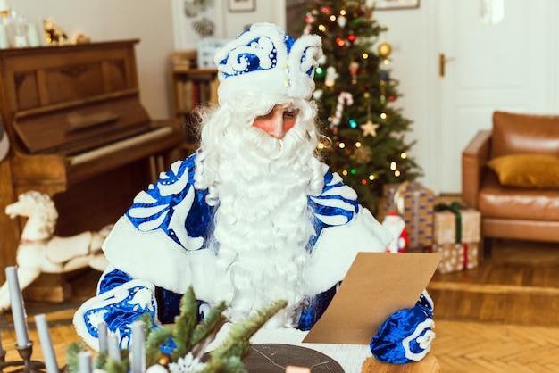 Portret szczęśliwy ojciec frost siedzi w swoim pokoju w domu w pobliżu choinki i czyta list bożonarodzeniowy