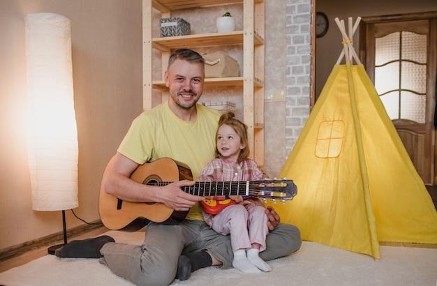 Portret szczęśliwy ojciec z gitarą w dłoniach i małą dziewczynką siedzącą na kolanach ojca. wspólne gry rodzinne.