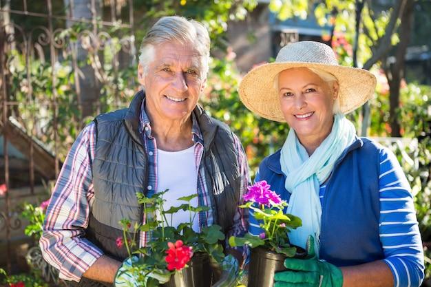 Portret szczęśliwy pary mienie puszkował rośliny przy ogródem