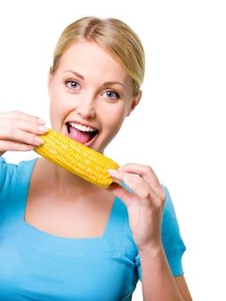 Portret szczęśliwy piękna dziewczyna gryzie surową kukurydzę