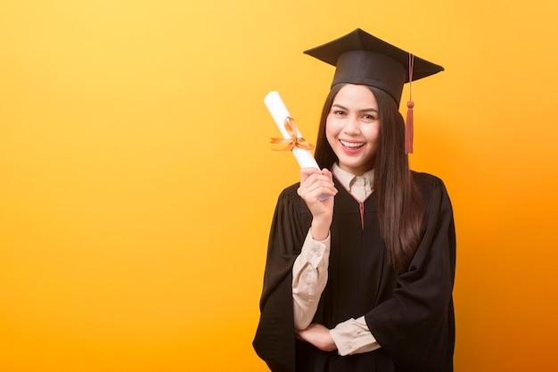 Portret szczęśliwy piękna kobieta w sukni ukończeniu trzyma świadectwo edukacji na żółtym tle