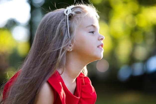 Portret szczęśliwy piękne dziecko dziewczyna na zewnątrz, ciesząc się ciepły słoneczny letni dzień.