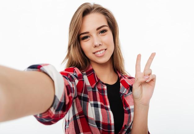 Portret szczęśliwy pięknej dziewczyny w kraciastej koszuli przy selfie