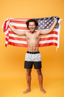 Portret szczęśliwy podekscytowany afrykański mężczyzna trzyma flagę usa