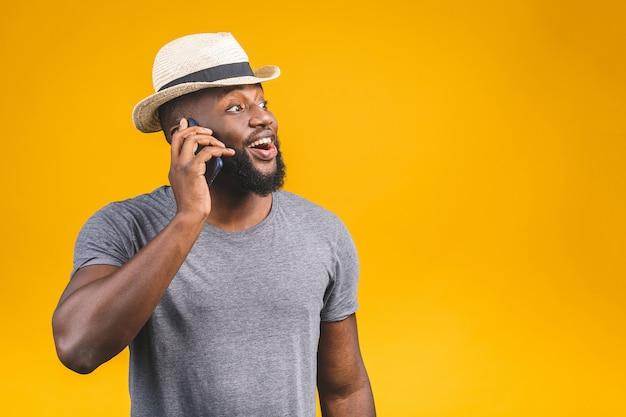 Portret szczęśliwy podróż amerykanina afrykańskiego pochodzenia facet opowiada na telefonie komórkowym.