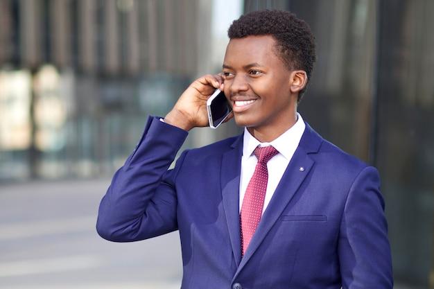 Portret szczęśliwy pozytywny młody biznesmen w formalnym garniturze rozmawia ze swojego telefonu komórkowego. czarny afroamerykanin afro amerykanin dzwoniący, rozmawiając na smartfonie i uśmiechając się