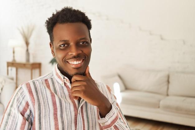 Portret szczęśliwy pozytywny młodych african american mężczyzna siedzi w pomieszczeniu z ręką na brodzie