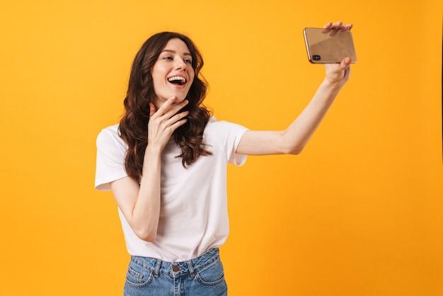 Portret szczęśliwy pozytywny optymistyczna uśmiechnięta młoda kobieta pozuje na białym tle nad żółtą ścianą weź selfie przez telefon komórkowy.