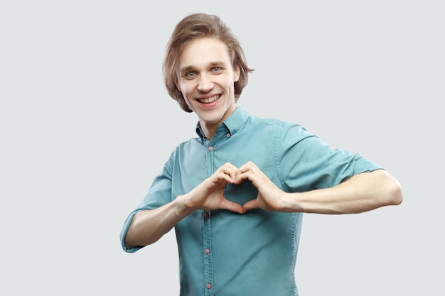 Portret szczęśliwy przystojny długowłosy blond młody człowiek w niebieska koszula dorywczo stojący, toothy uśmiech, miłość serce gest ręka z toothy uśmiechem. kryty strzał studio, na białym tle na jasnoszarym tle.