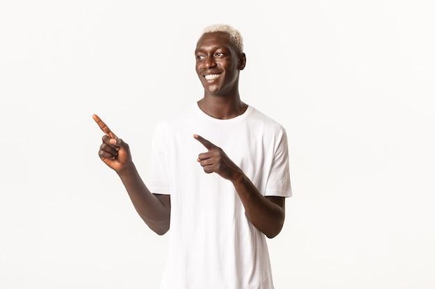 Portret szczęśliwy przystojny facet afroamerykanin z blond włosami, wskazując palcami w lewym górnym rogu i patrząc na logo zadowolony